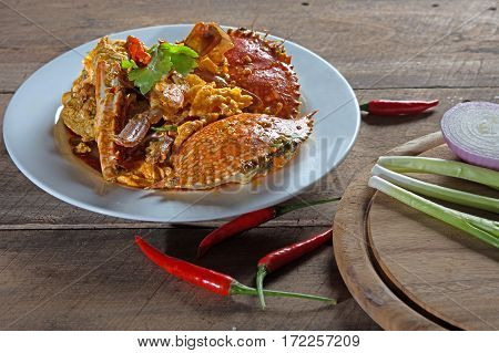 Crab curry in Thai infused red coconut curry sauce on wood background and Chopping Wood, selective focus
