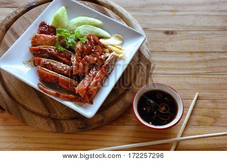 Peking duck is served on a white plate.