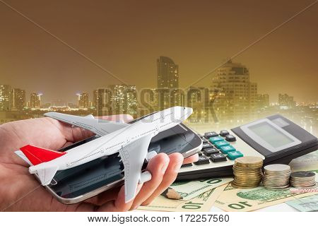 Hand hold cell phone with airplane model on banknotes background