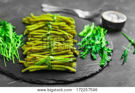 Cooked boiled stewed green beans tied in bundles of green onions. Ingredients for the green beans pickled onions and fresh arugula. Black concrete background.