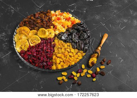 Assortment of dried fruit and candied fruit. Fruits figs prunes raisins papaya pineapple cranberries are laid out in rows on black concrete background in the glass dish. Dry fruits in measuring spoon.