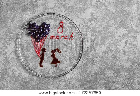 Card to female spring holiday 8th of March. On glass plate concept congratulations for March 8. Chocolate Man gives girl bunch of balloons from grapes red inscription