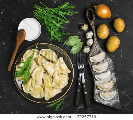 Dumplings with potatoes in plate on black background. On board cooking raw dumplings with potatoes. Ingredients for dumplings onions arugula eggs bay leaf potatoes sour cream sauce. Top view.