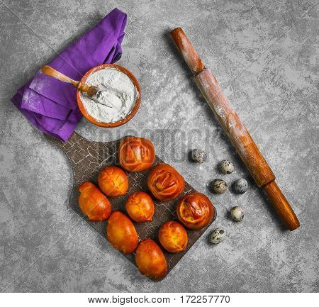 Preparing buns bread. Ingredients for cooking homemade buns bread wheat flour in bowl quail eggs wooden rolling pin. Fresh buns in board on gray concrete background.