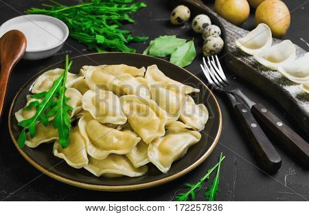 Dumplings with potatoes in plate on black background. On board cooking raw dumplings with potatoes. Ingredients for dumplings with potatoes onions arugula eggs bay leaf potatoes sour cream sauce.