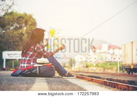 Traveler women wearing backpack holding map waiting for a train.
