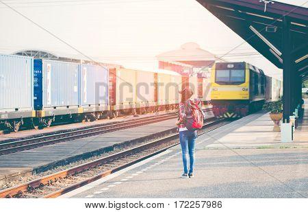 Traveler women walking alone Carrying luggage and waits train on railway station