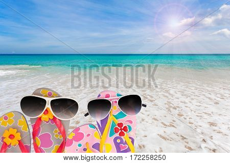 beach shoes with sunglasses on tropical sea and sky background