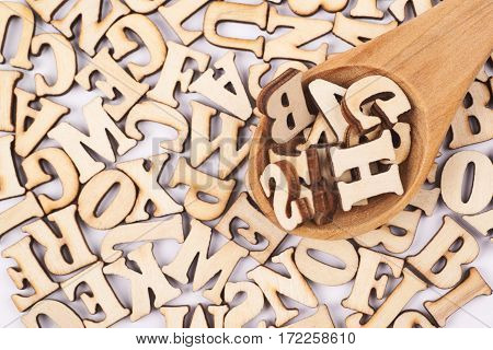 Surface covered with the multiple wooden letters and wooden spoon over it as a creative education backdrop composition