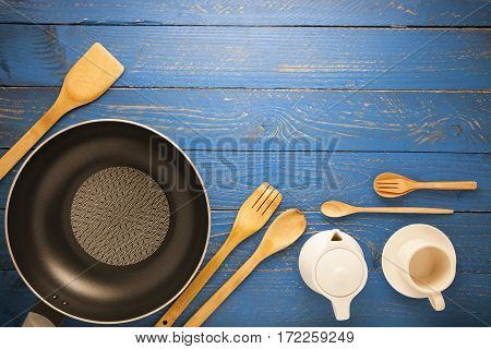 Black frying pan with cooking utensils on blue wood table background