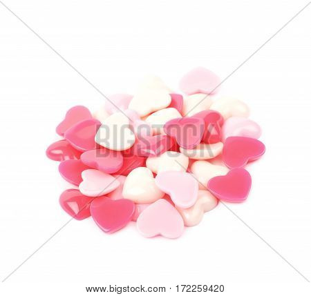 Pile of pink and glossy heart shaped decorational beads isolated over the white background