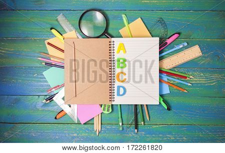 notebook with school supplies on blue wood backgroundconcept back to school background