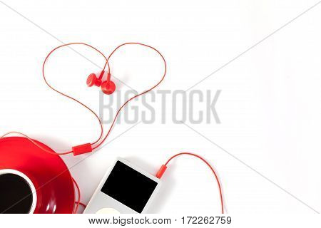 red coffee cup with music player and red earphone on white backgroundValentine's day concept.