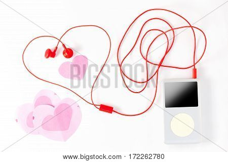 music player with red earphone and paper note on white backgroundValentine's day concept.