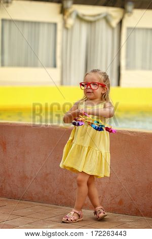 Cute little girl in glasses holds in hands of the pinwheel. A walk in the summer park near the city fountain. Summer vacation. Outdoor Activities.
