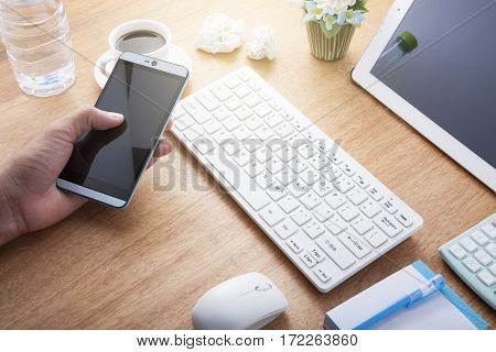 Hand man use tablet smartphone with Office desk wood table of Business workplace and business objects