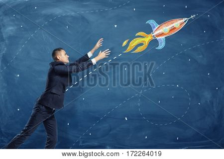 A businessman pulling up his hands to a flying through the sky rocket painted on a blackboard. Childish dreams. Aspiration to self-fulfillment. Reality and wishes.