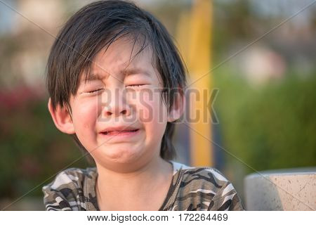 Close up of Asian child crying in the park