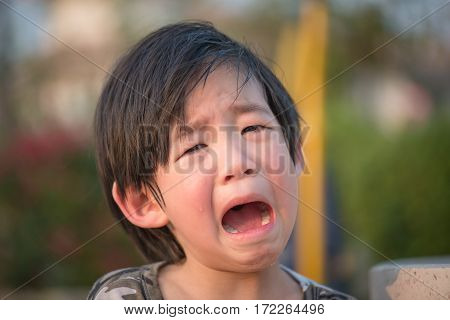 Close up of Asian child crying in park