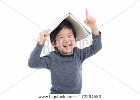 Cute Asian boy with book on head thinking on white background isolated