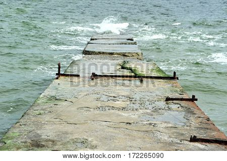 Wave of the sea and old concrete pier
