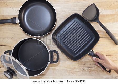 Hand holding a cast iron frying pan on wood background