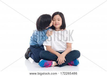 Cute Asian boy kissing his sister on white background isolated
