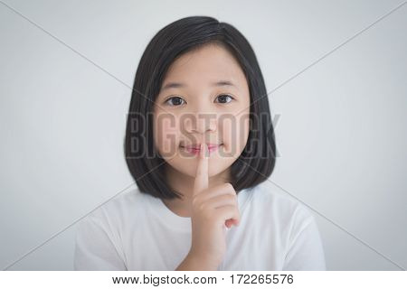 portrait of beautiful Adsian girl with a finger on her lips showing to keep silence