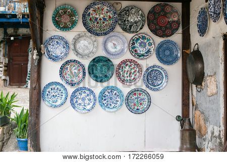 White Wall Decorated With Many Ceramic Plates