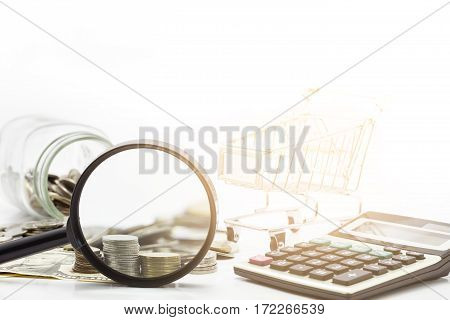 Magnifier with stacks of coins and dollar banknote on white background