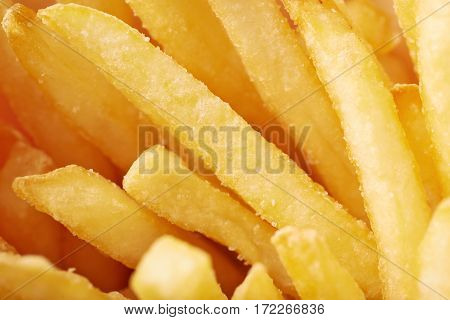 Close-up fragment of a multiple french fries potato chips as a food backdrop composition