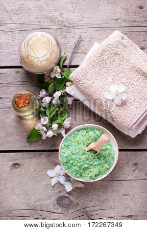 Spa products. Sea salt in bowl towels aroma oil in bottle and flowers on vintage wooden background. Selective focus.