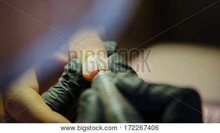 Professional manicure - nail master in beauty shop - telephoto close up, horizontal