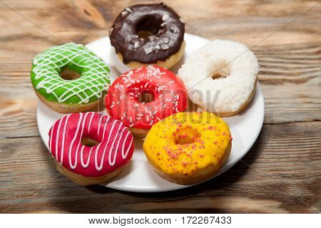 Assorted Colorful Donuts on wooden rustic table