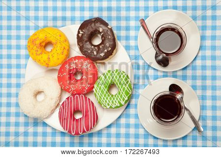 cups of tea and a donut on a blue table