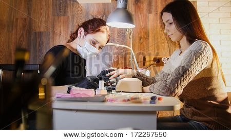 Nail master in medical mask doing professional manicure for white caucasian model, cosmetic salon, telephoto