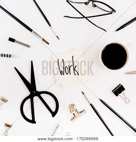 White office desk frame with word work and supplies. Coffee scissors pen clips glasses and office supplies on white background. Flat lay top view office table desk.