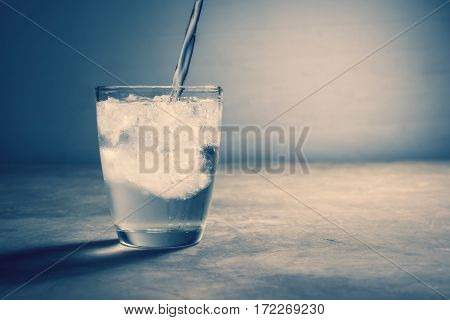 Abstract Water Pouring Into Glass Of Water With Ice In Vintage Color.