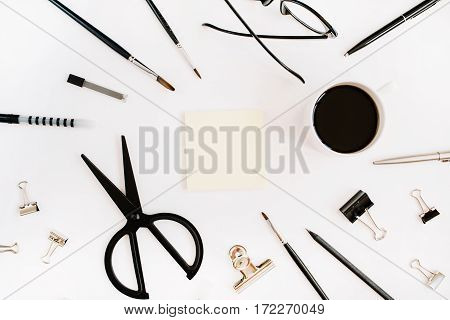 White office desk frame with blank paper and supplies. Coffee scissors pen clips glasses and office supplies on white background. Flat lay top view office table desk.