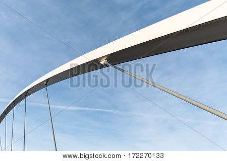 Closeup of a bridge support structure details with blue and partly cloudy sky as background
