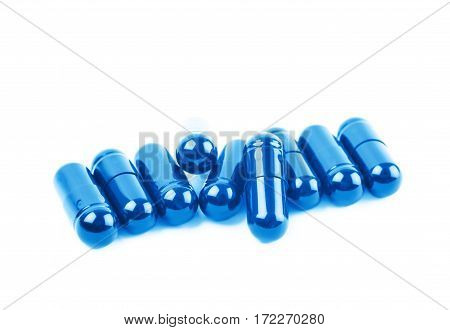 Pile of softgel blue capsule pills isolated over the white background