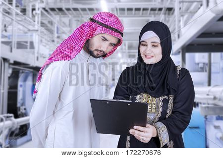 Image of female Muslim employee is holding a clipboard while showing and explaining report to her manager in the factory