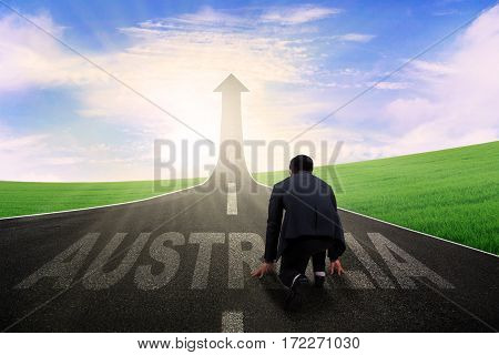 Back view of young businessman in ready position to run toward arrow upward with Australia word on the highway