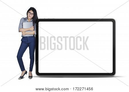 Full length of young businesswoman leaning on big board while holding a laptop isolated on white background
