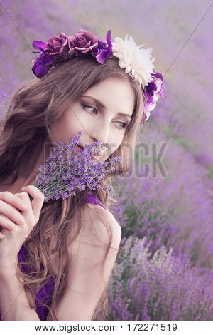 Young woman with long blonde hair in a purple dress enjoying the beauty of nature in the lavender field