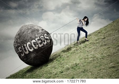Portrait of beautiful businesswoman pulling big stone with success word while climbing on the hill