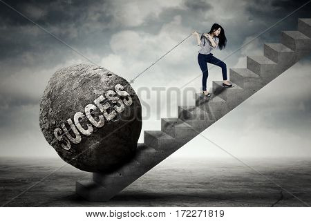 Image of young businesswoman pulling a boulder with success word while climbing on the stair