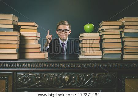 Smart school boy sitting at the table with many books and one green apple. Child dressed in school uniform and glasses. Blackboard. Student. Concept of education. Looking at camera