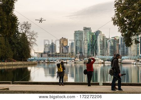 Vancouver Canada - January 28 2017: Vancouver city skyline with boats in harbour and seaplane coming in to land