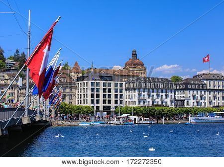 Lucerne, Switzerland - 8 May, 2016: people and flags on the Seebrucke bridge, buildings along Lake Lucerne. Lucerne is a city in central Switzerland, it is the capital of the Swiss Canton of Lucerne and the capital of the district of the same name.